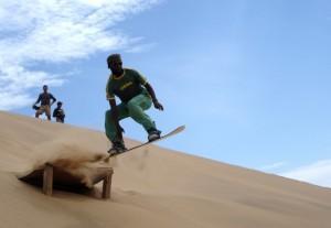Von einer Sprungschanze in der Namib-Wüste hebt Sandboarding-Lehrer Raymond Inichab hebt ab.