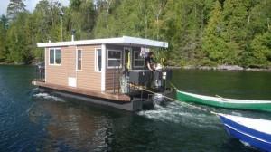 Hausboot mit Kanus im Schlepptau