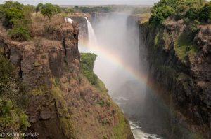 Die Sonne zeichnet Regenboegen in die Gischt der Victoria Falls