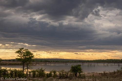 Ein Gewitter braut sich ueber Mandavu Dam im Hwange National Park zusammen
